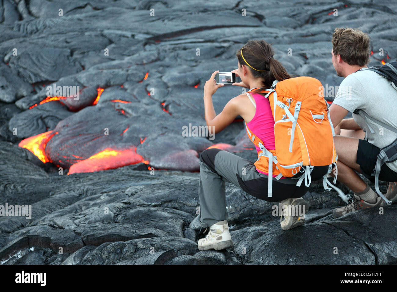 Tourists taking photo of flowing lava from Kilauea volcano around Hawaii volcanoes national park, USA - Stock Image