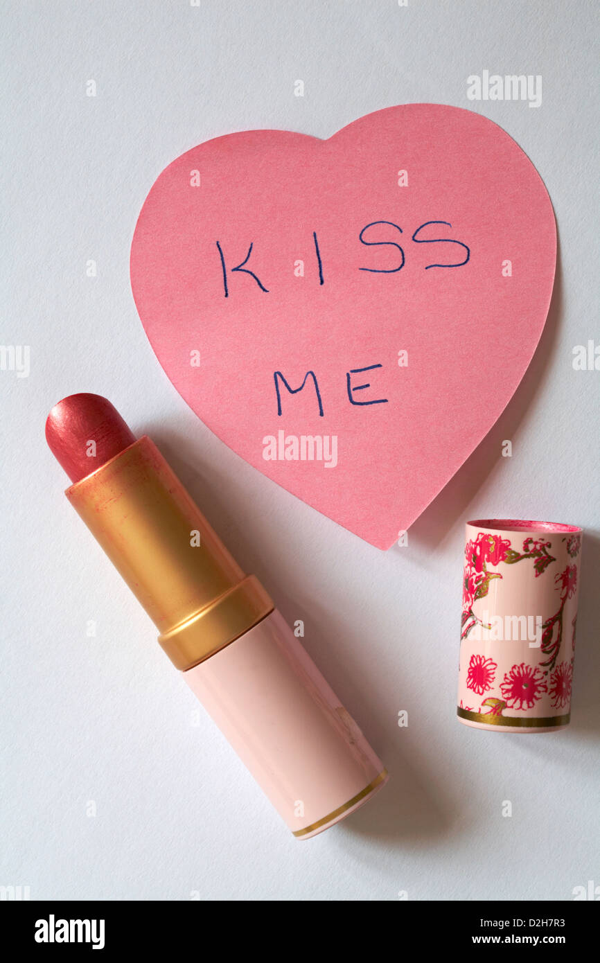 kiss me message written on pink heart shaped post it note pad with lipstick isolated on white background - Stock Image