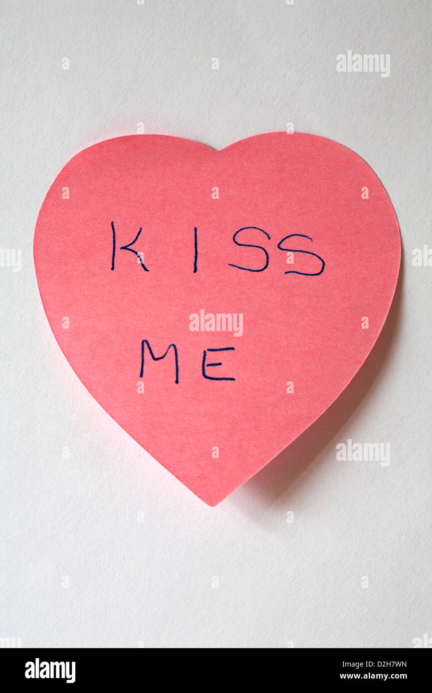 kiss me message written on pink heart shaped post it note pad isolated on white background - Stock Image