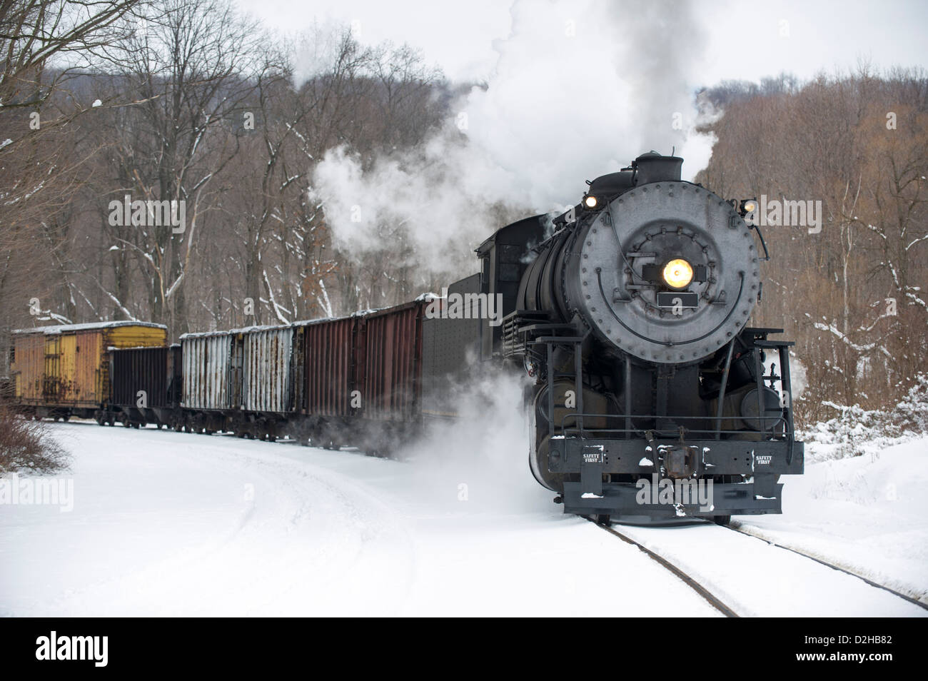 Steam locomotive pulling train rounding curve in winter snow pushing strong smoke plume, historical reenactment - Stock Image