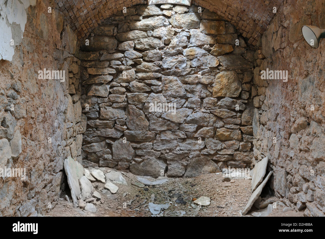 Prison cell rock wall of natural stone with overhead skylight, abandoned and deteriorating Eastern State Penitentiary - Stock Image