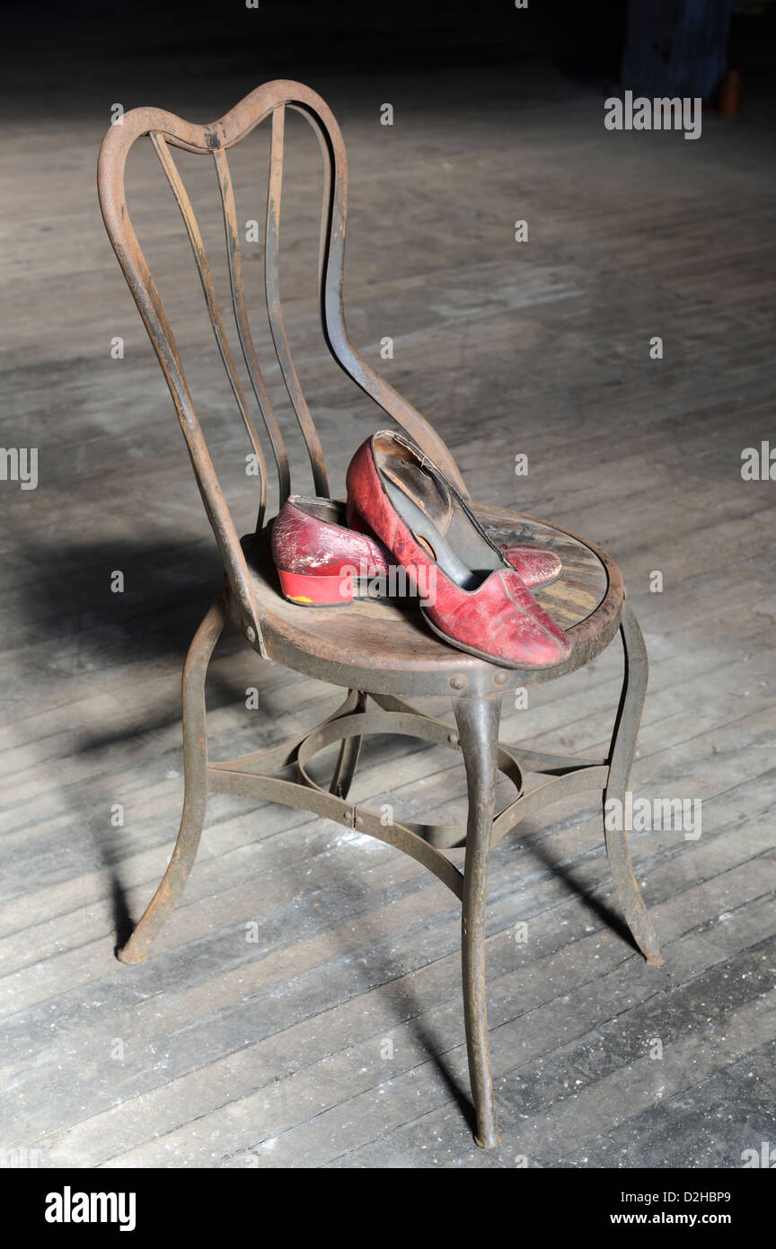 Old red worn out shoes on rusty metal chair with dirty wooden floor for a background. - Stock Image