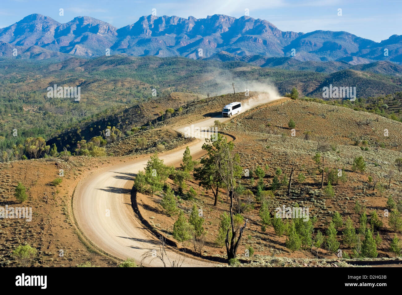 An outback tour bus makes its way along a dusty road in South Australia's picturesque Flinders Ranges. - Stock Image