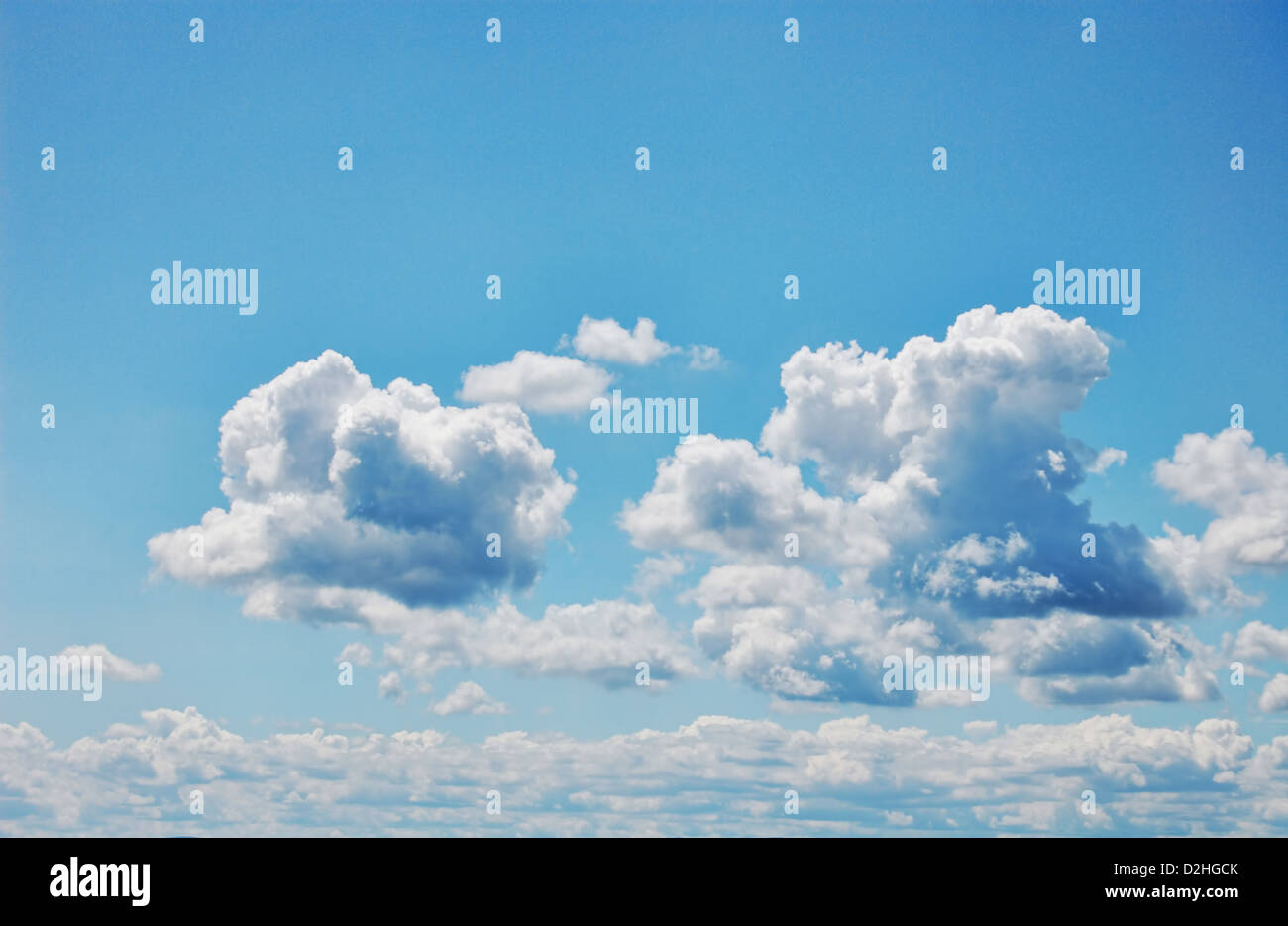 Blue sky with fluffy white clouds. Wide format. Photographic Image. - Stock Image