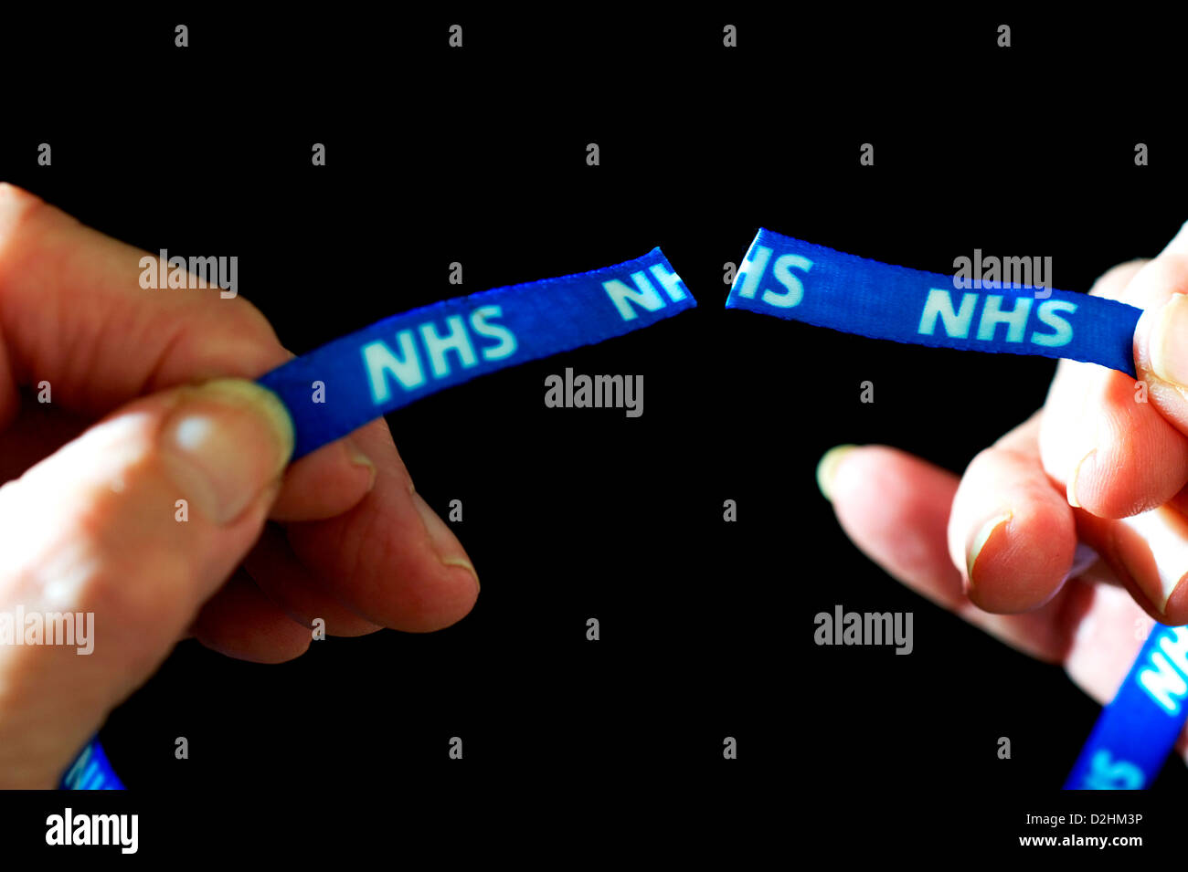 Two NHS ribbons being held apart after they have been cut. NHS Efficiency Savings. On black background - Stock Image