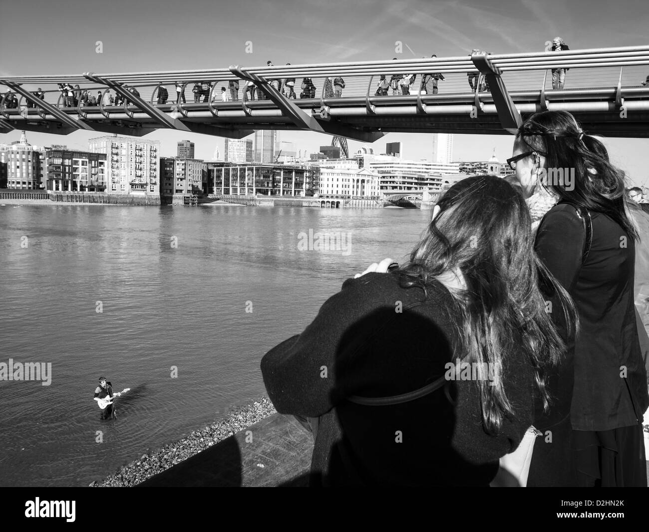 a boy playing on guitar in Thames under Millenium bridge - Stock Image