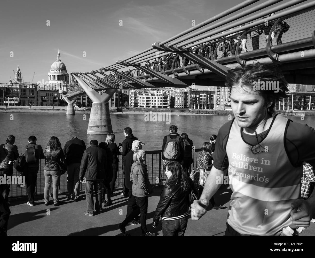 a young man running under millenium bridge in a sunny day Stock Photo