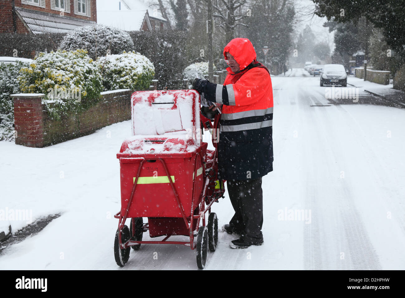 Postman delivers the mail in London in a January snowfall. - Stock Image
