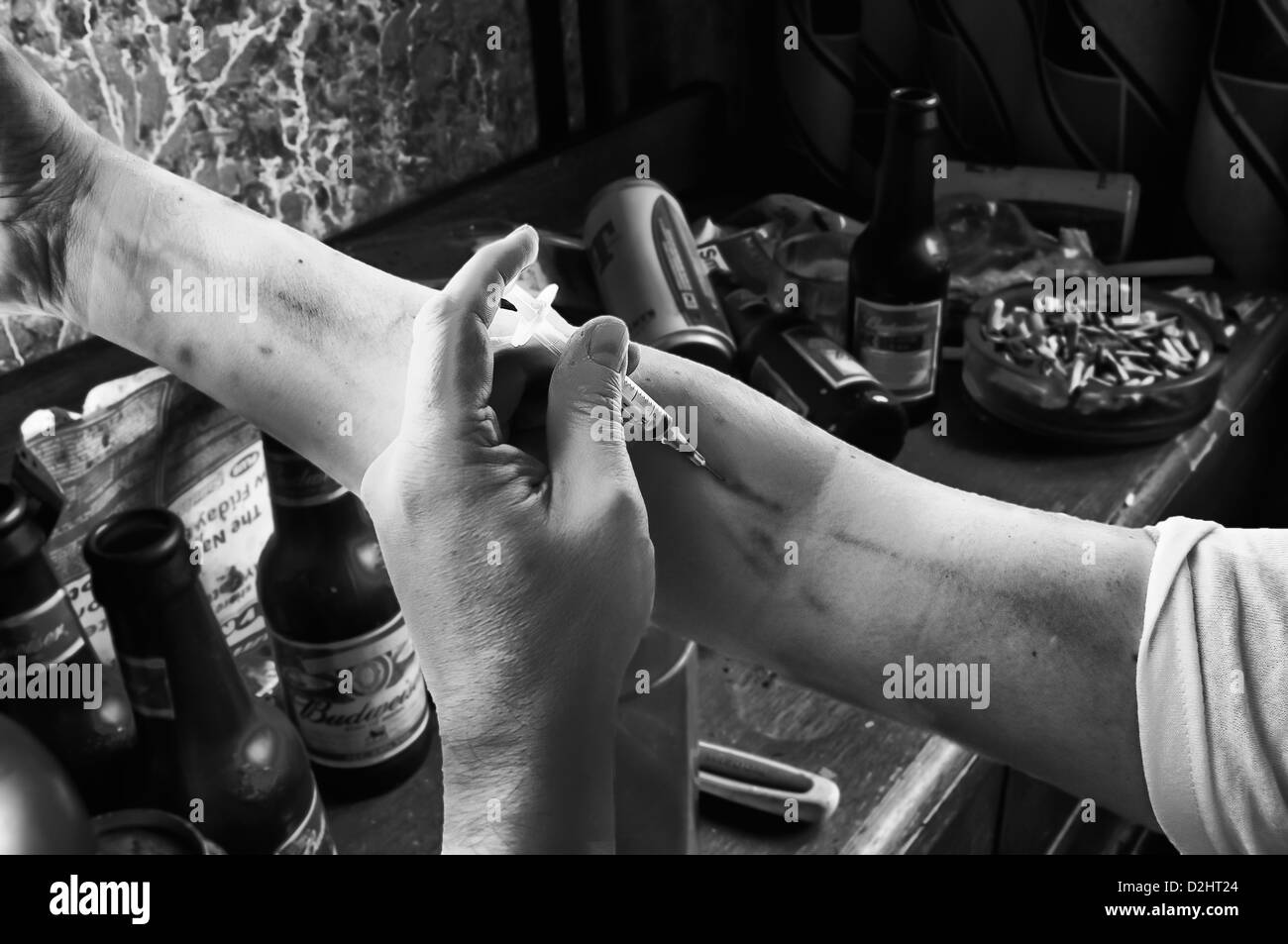 Heroin drug user injects his arm using a hypodermic syringe in a dirty bedroom (B&W - see D2HT21 for colour - Stock Image