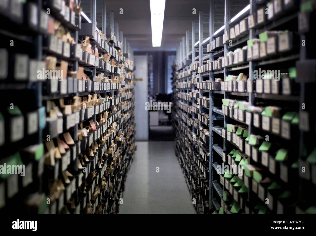 A view along a corridor of shelves filled with filing boxes and index cards of missing or killed German soldiers - Stock Image