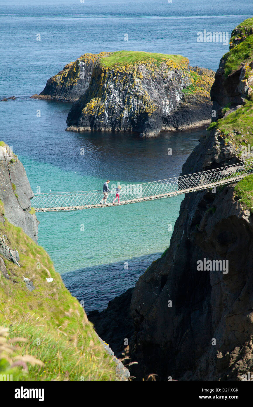 People crossing Carrick-a-rede Rope Bridge, County Antrim, Northern Ireland. - Stock Image