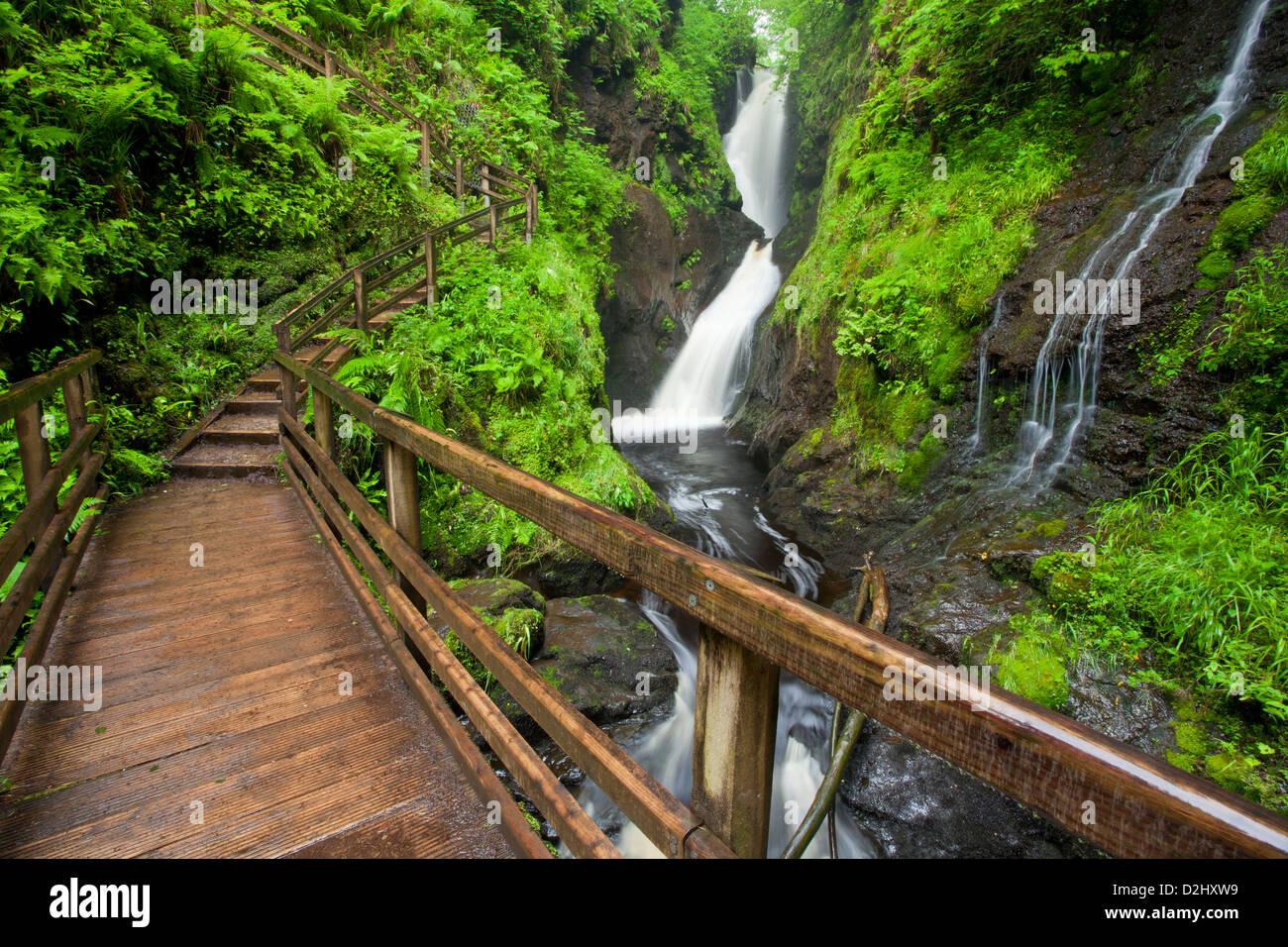 Walkway beneath Ess-na-Larach waterfall, Glenariff Forest Park, County Antrim, Northern Ireland. - Stock Image
