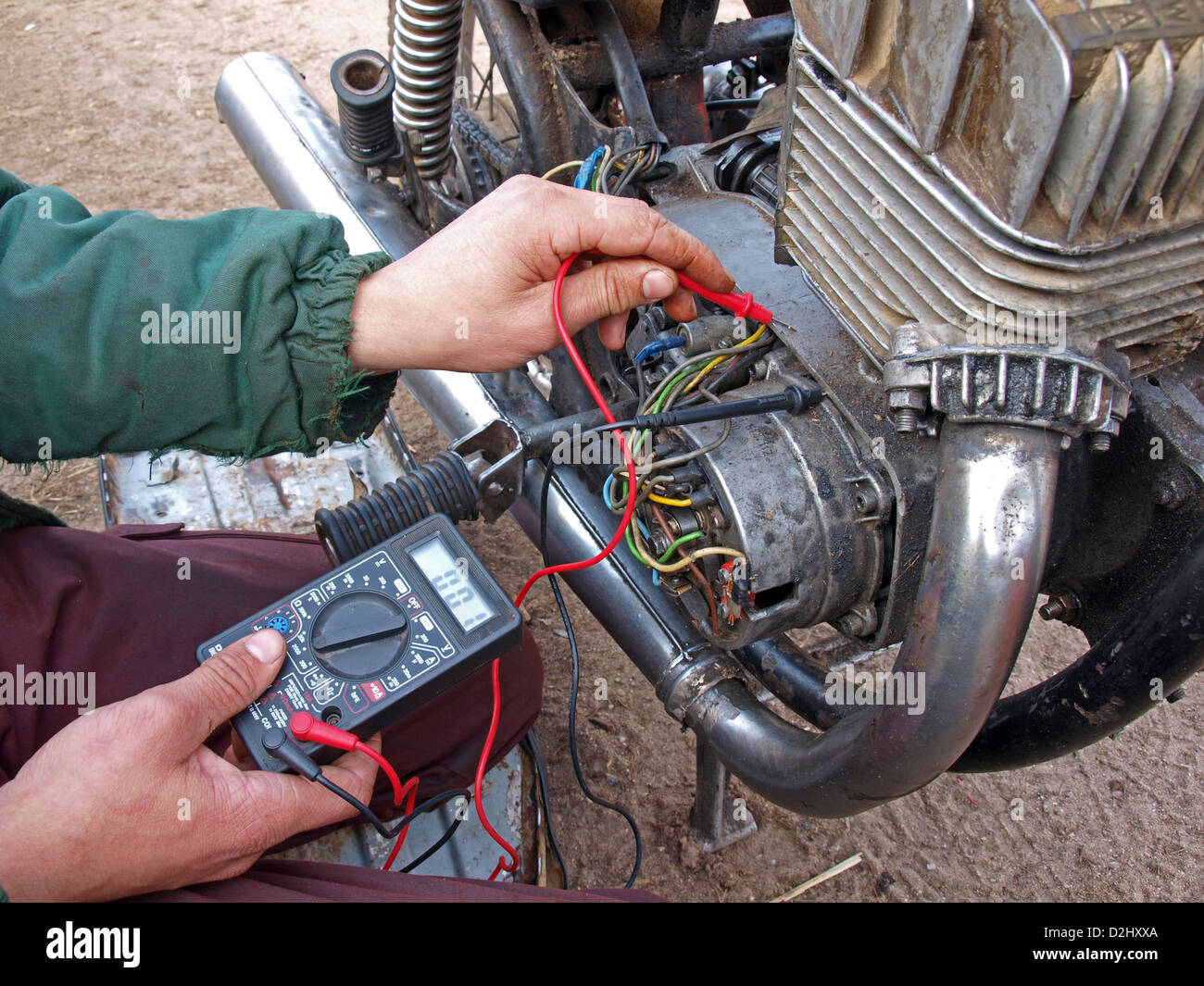 Young man with multimeter testing motorcycle engine - Stock Image