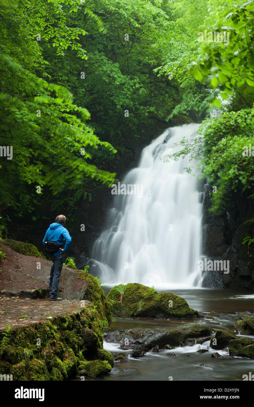 Person beneath Glenoe Waterfall, County Antrim, Northern Ireland. - Stock Image