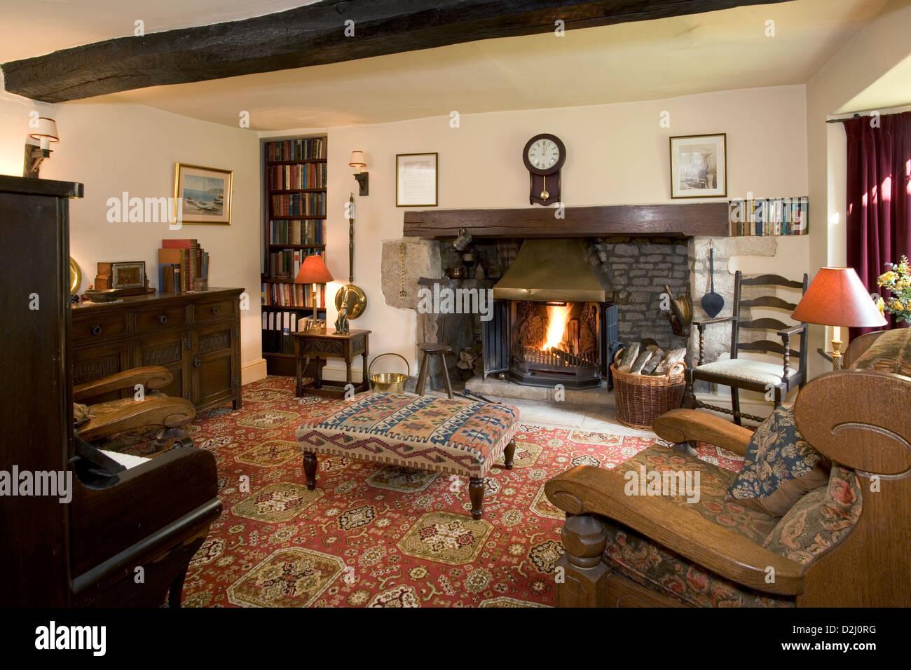 Traditionally furnished cottage sitting room with log burning stove. - Stock Image