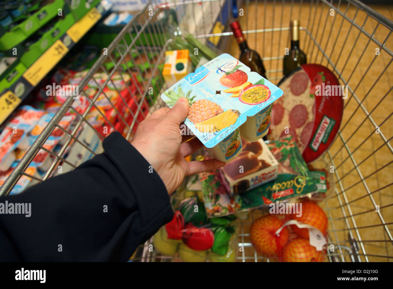 Bremen, Germany, a man grabs fruit yogurts in a shopping cart - Stock Image