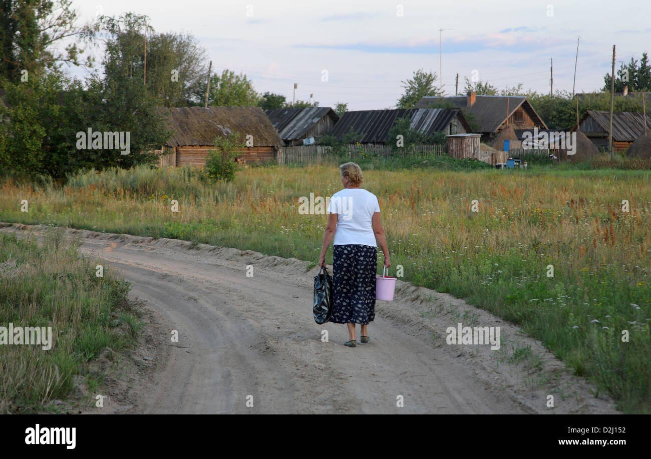 Kalnik Belarus, a woman walks along a country lane Stock Photo