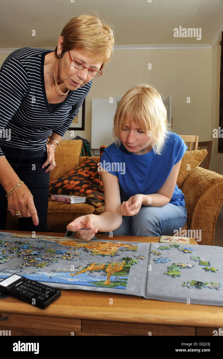 A young women with Learning Disabilities enjoys doing a jigsaw with her support worker, Skipton, North Yorkshire. - Stock Image
