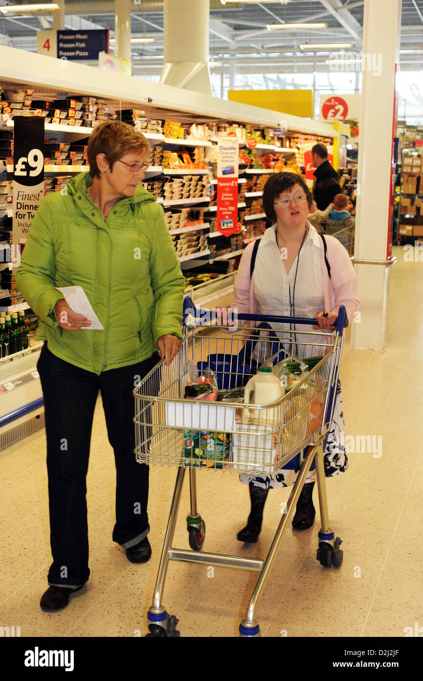 A young women with Learning Disabilities go shopping with their support worker, Skipton, North Yorkshire. - Stock Image