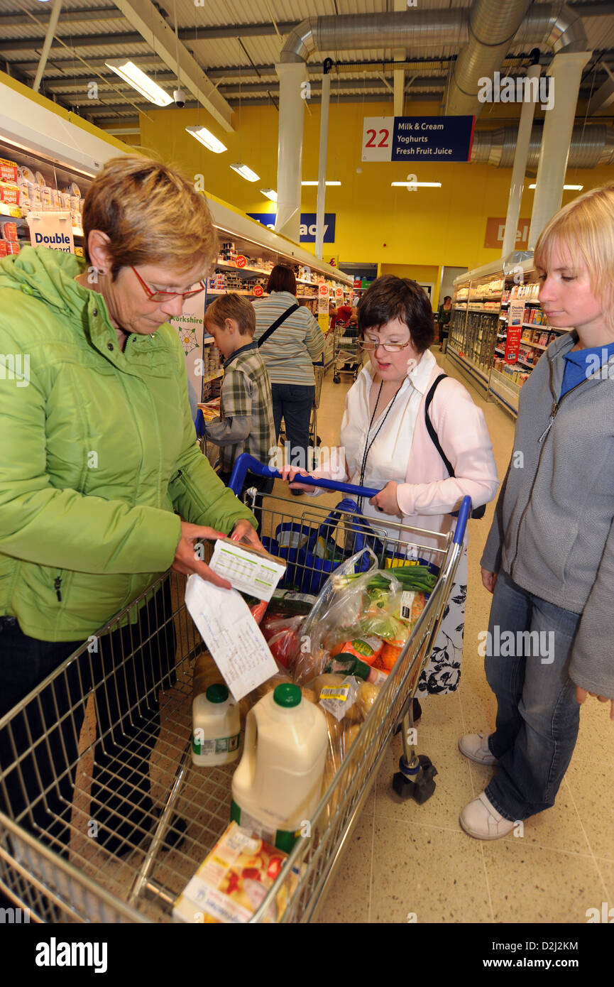 Two young women with Learning Disabilities go shopping with their support worker, Skipton, North Yorkshire. - Stock Image