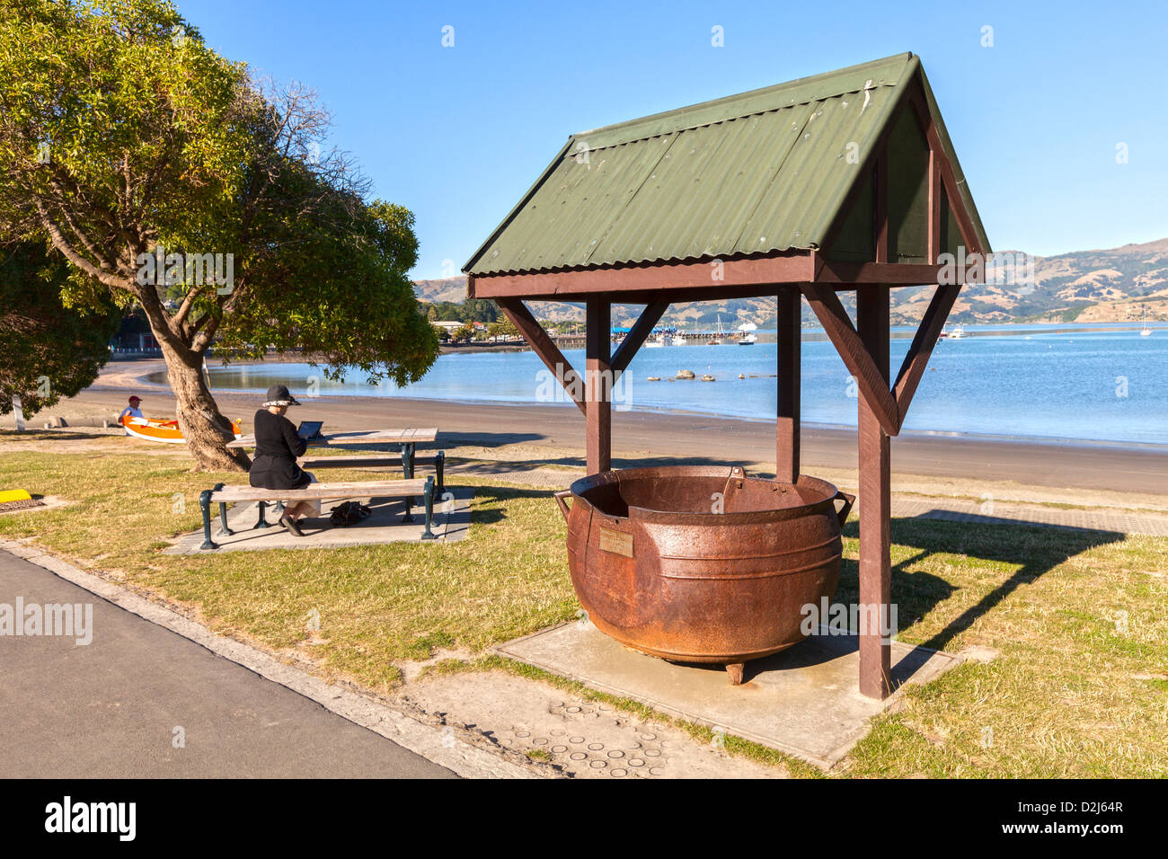 A try pot, relic of Akaroa's days as a whaling station, on the waterfront of the harbour. Woman sitting on bench - Stock Image