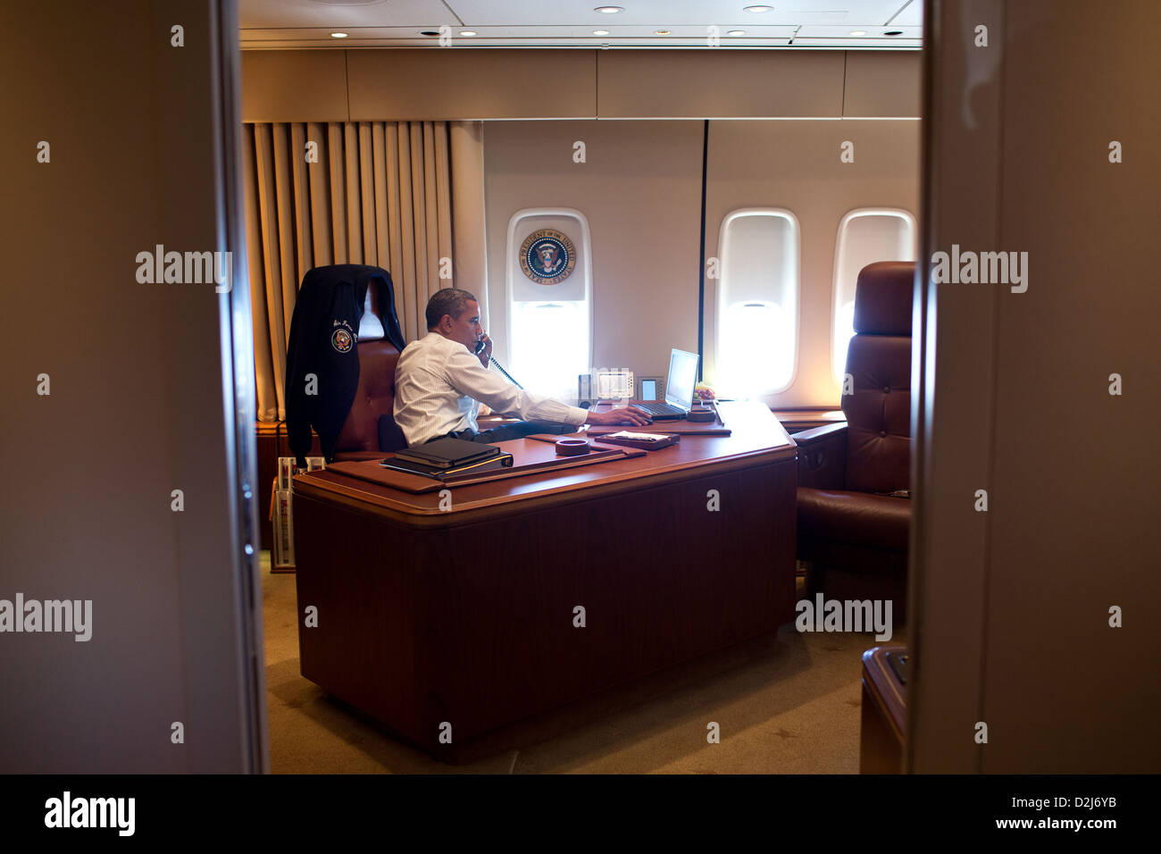 President Barack Obama holds a conference call with advisors aboard Air Force One during a flight to Portland, Oregon - Stock Image
