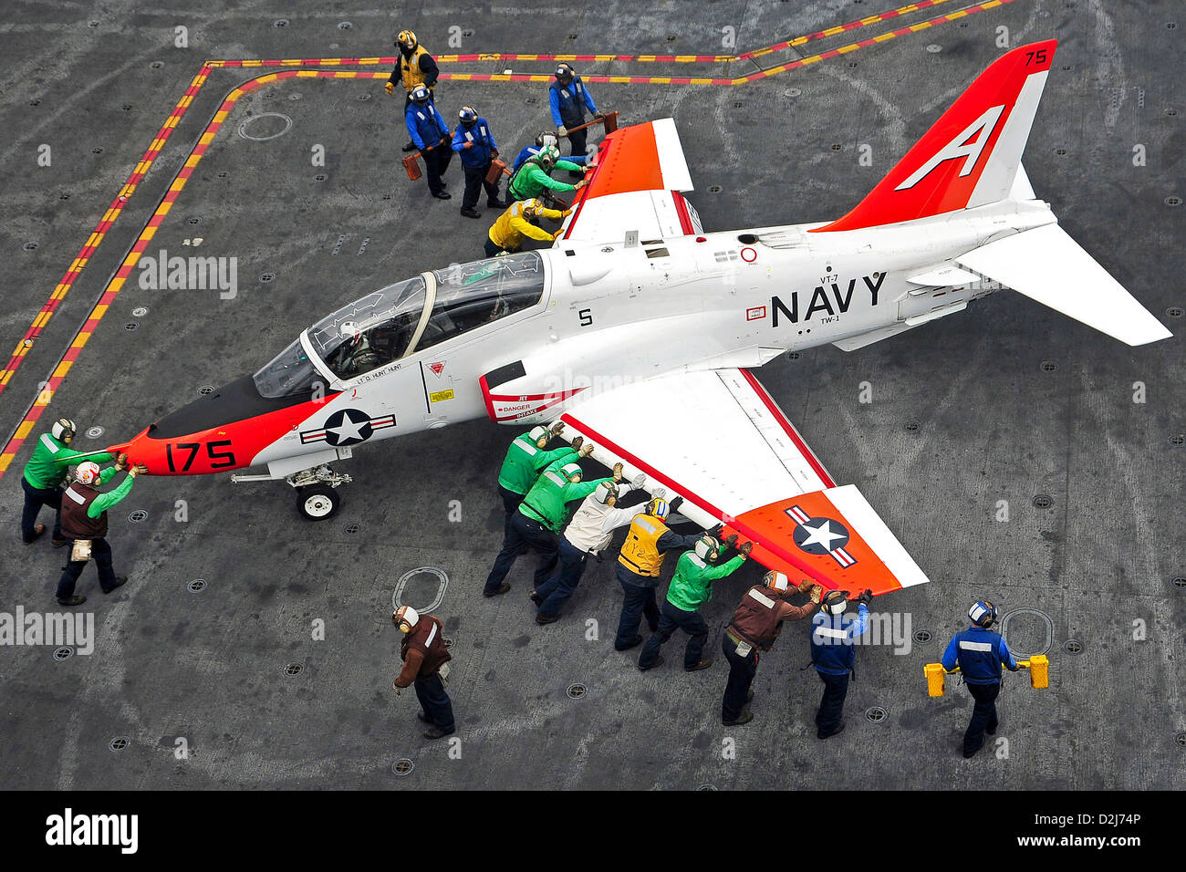 US Navy Sailors push back a T-45C Goshawk training aircraft on the flight deck of the aircraft carrier USS Harry - Stock Image