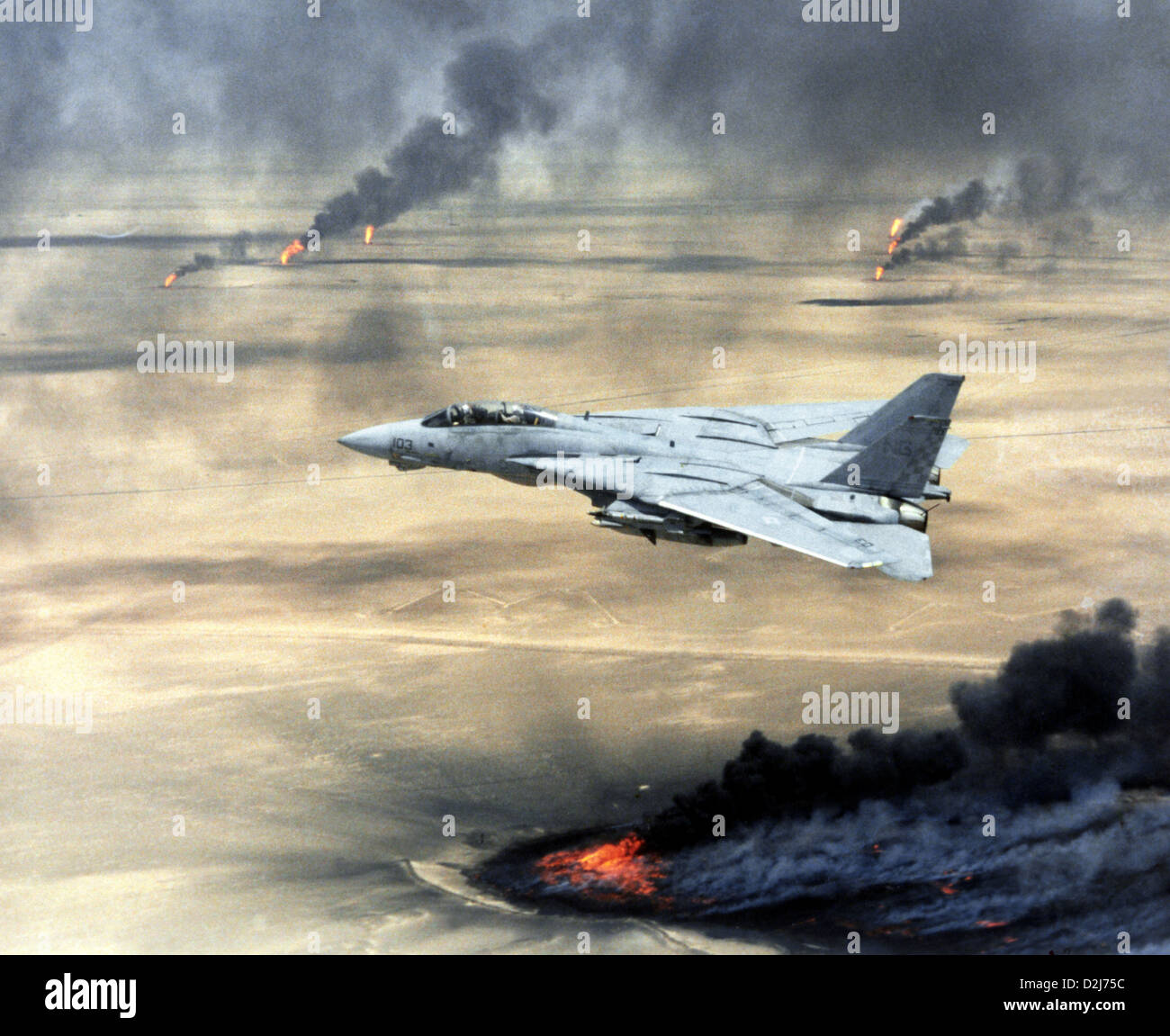 A US Navy F-14A Tomcat in flight over burning Kuwaiti oil wells during Operation Desert Storm February 1, 1991 - Stock Image