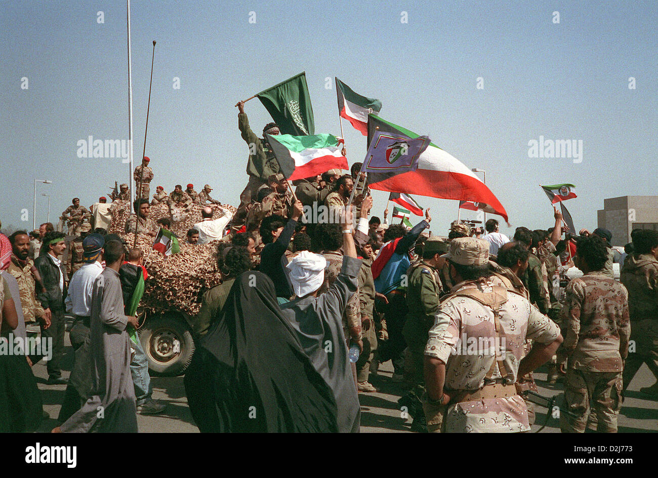 Civilians and coalition military forces wave Kuwaiti, Saudi Arabian and other flags as they celebrate the retreat - Stock Image