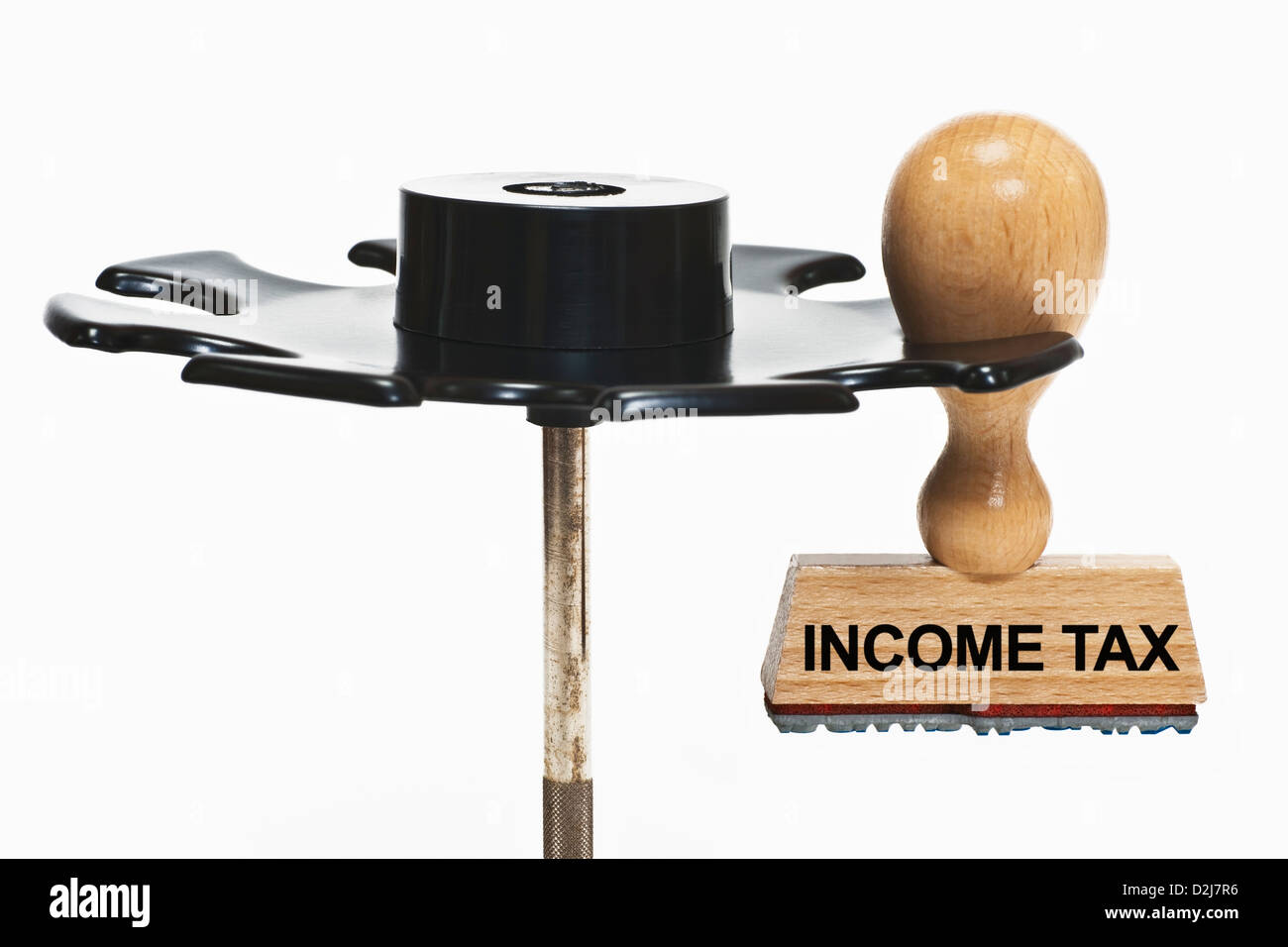 a stamp with the inscription income tax hangs in a stamp rack, background white - Stock Image