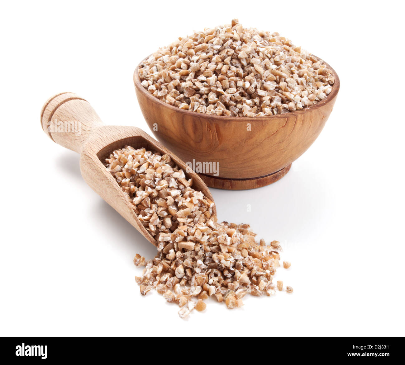 wheat groats in a wooden bowl isolated on white background - Stock Image