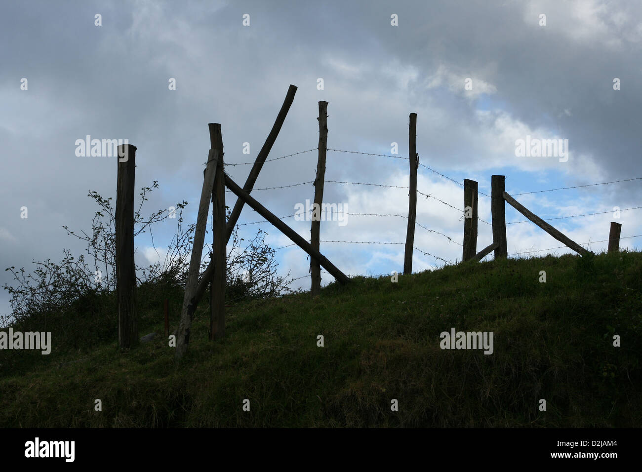 A wood and barbed wire fence stretching over a hill in a farmers ...