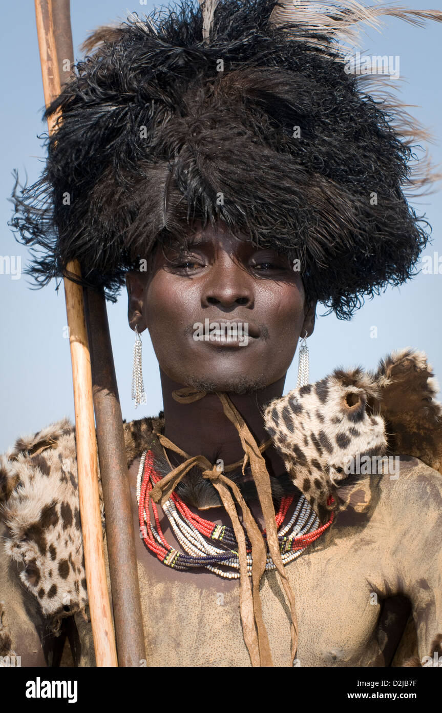 Close up of Dassenech man wearing cheetah cape and headdress of feathers - Stock Image