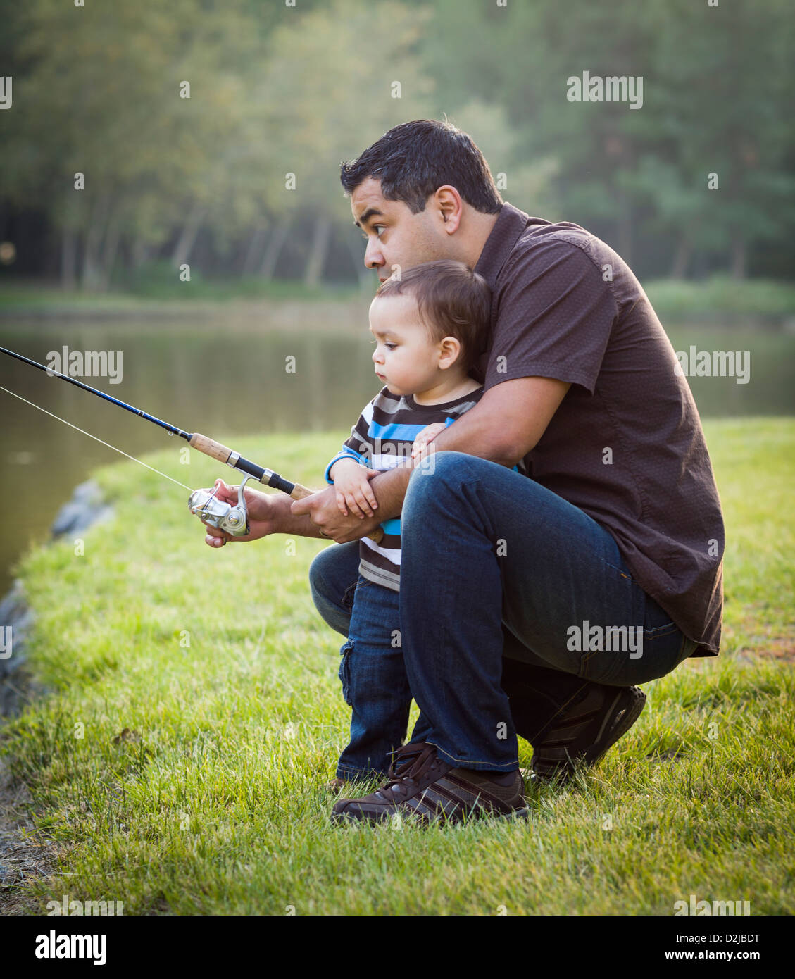 Happy Young Ethnic Father and Son Fishing at the Lake. - Stock Image