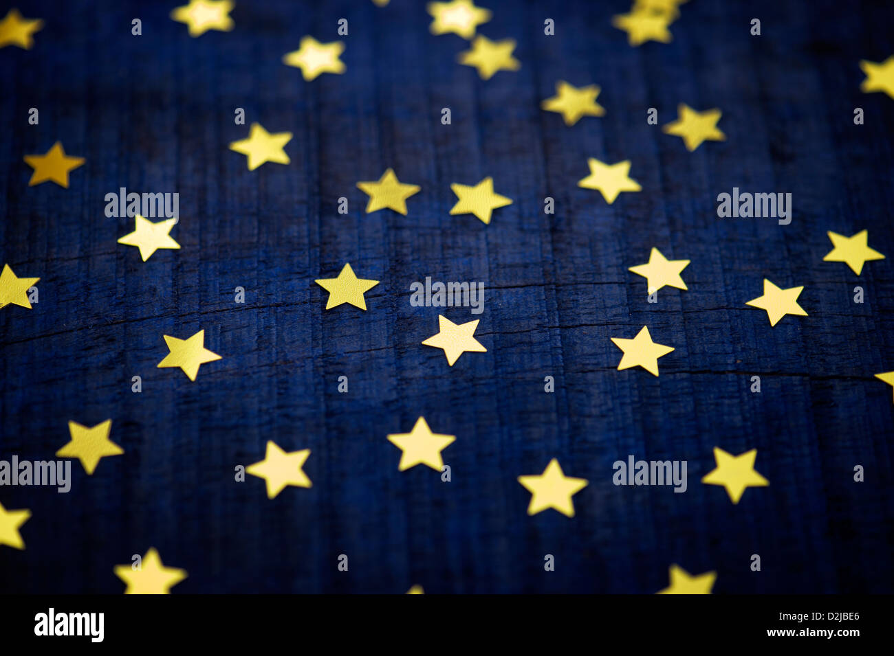 shiny gold stars on a dark blue wood background stock photo