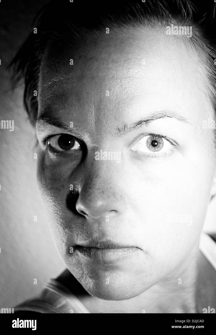 A black and white self portrait of a woman who portrays the darkness and light of an individual self. - Stock Image