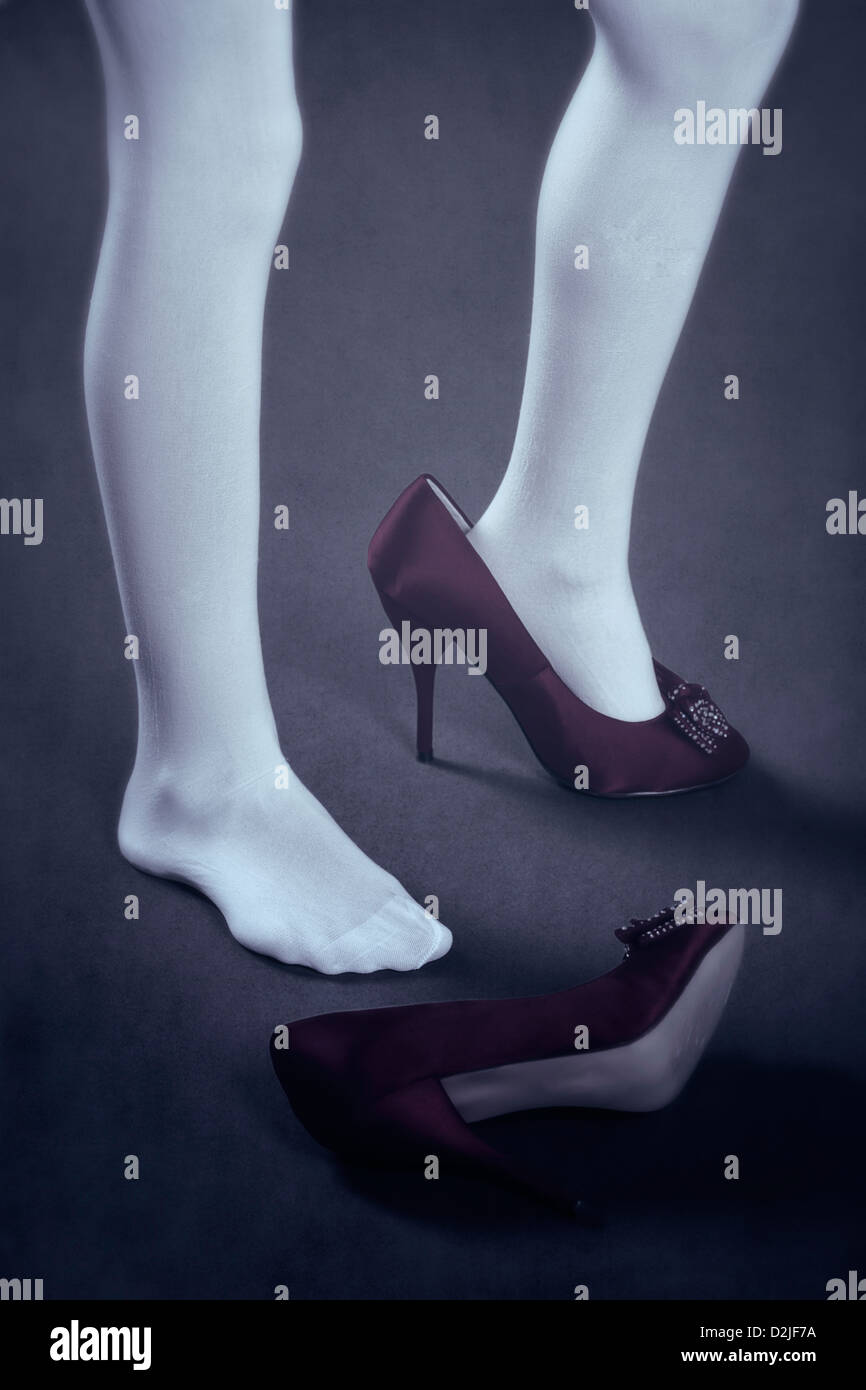 a girl in white stockings with too big shoes - Stock Image