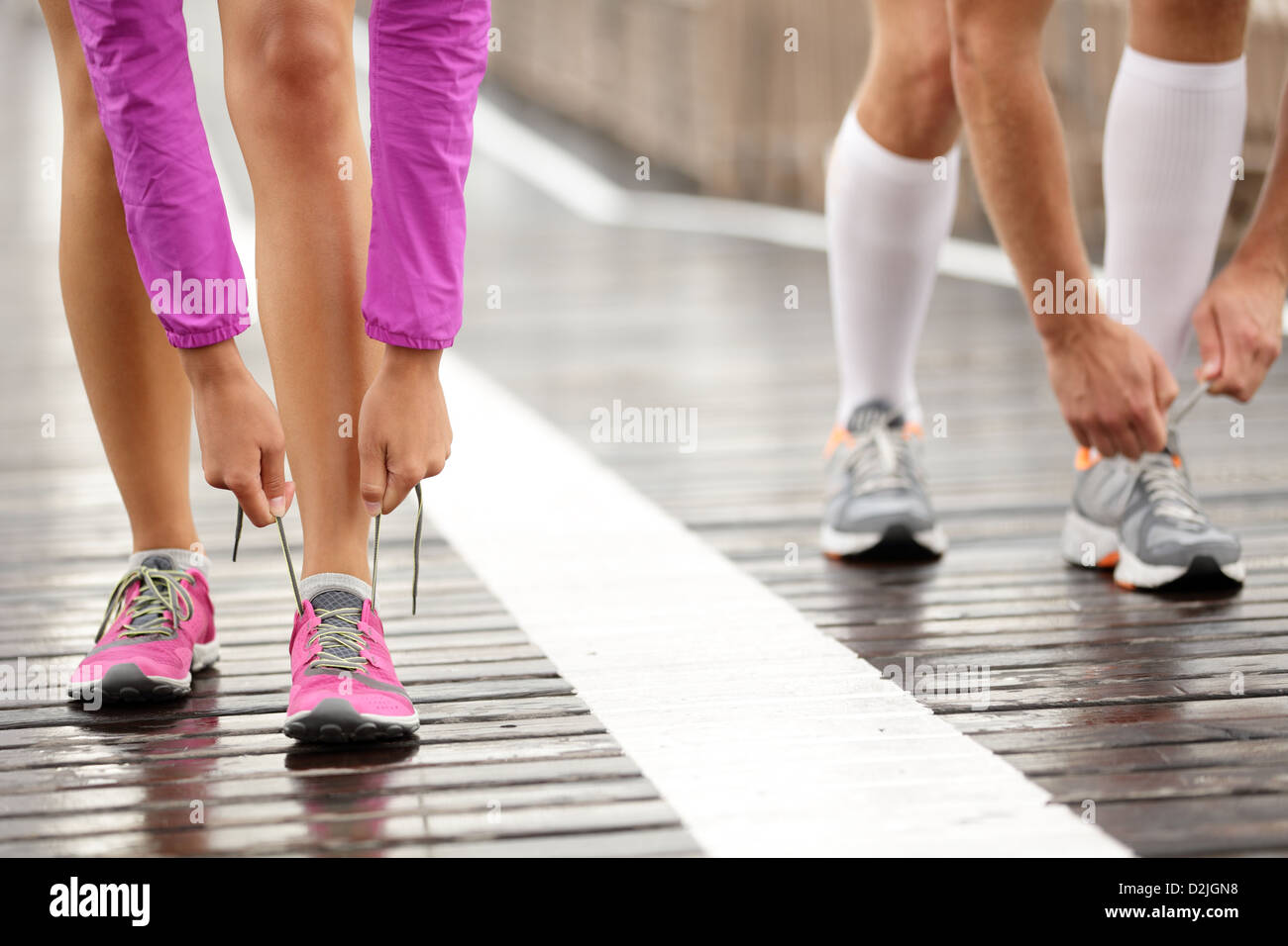 Low section of couple tying shoelaces while jogging on Brooklyn Bridge, New York - Stock Photo