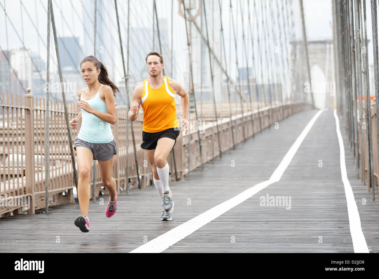 Full length of Asian woman and Caucasian man jogging on Brooklyn Bridge, New York City, USA Stock Photo