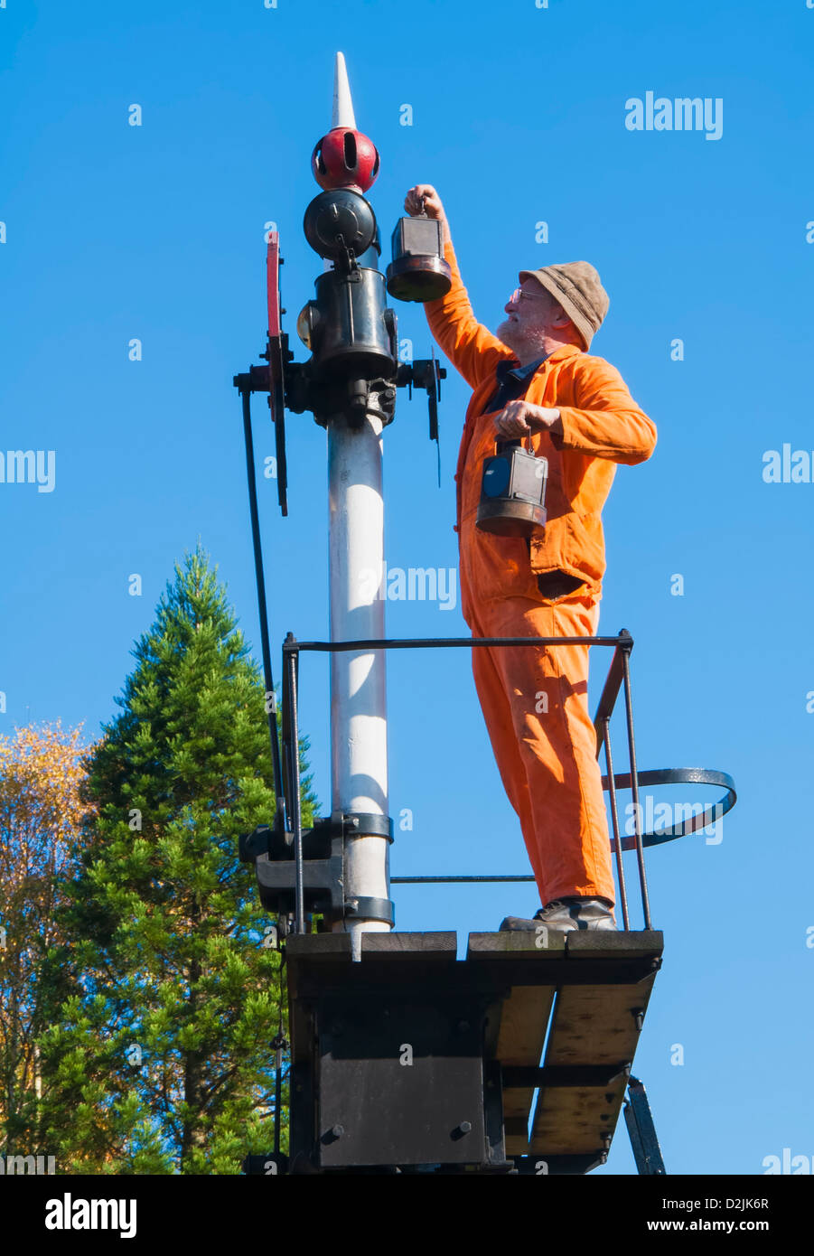 Steam railway enthusiast changing the signal lantern at the South Devon Railway's Buckfastleigh station - Stock Image