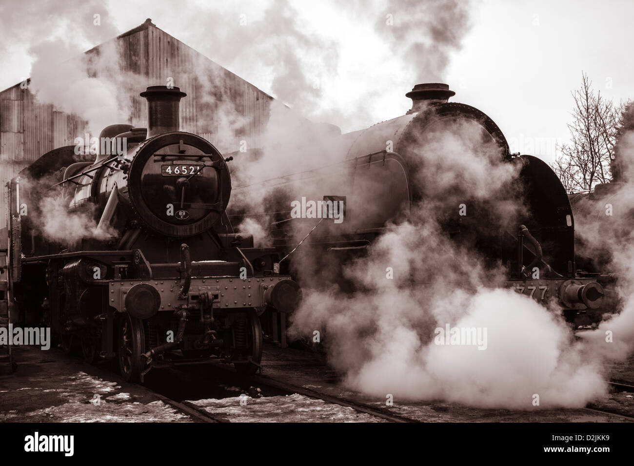 Steam locomotives outside engine shed Ivatt class number 46521 and King Arthur class Sir Lamiel number 30777 - Stock Image