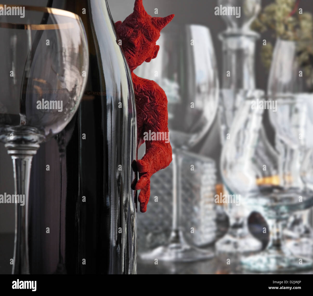 a little red devil peeks out from behind a bottle of wine. Some glasses are spread out on the inlaid table. - Stock Image