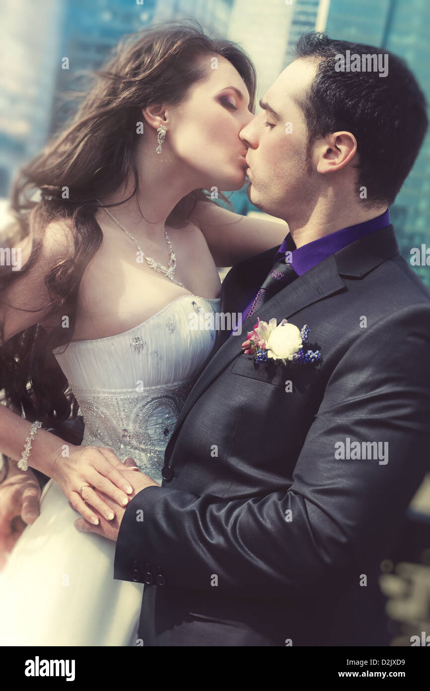 Young wedding couple kissing. Film style colors. - Stock Image