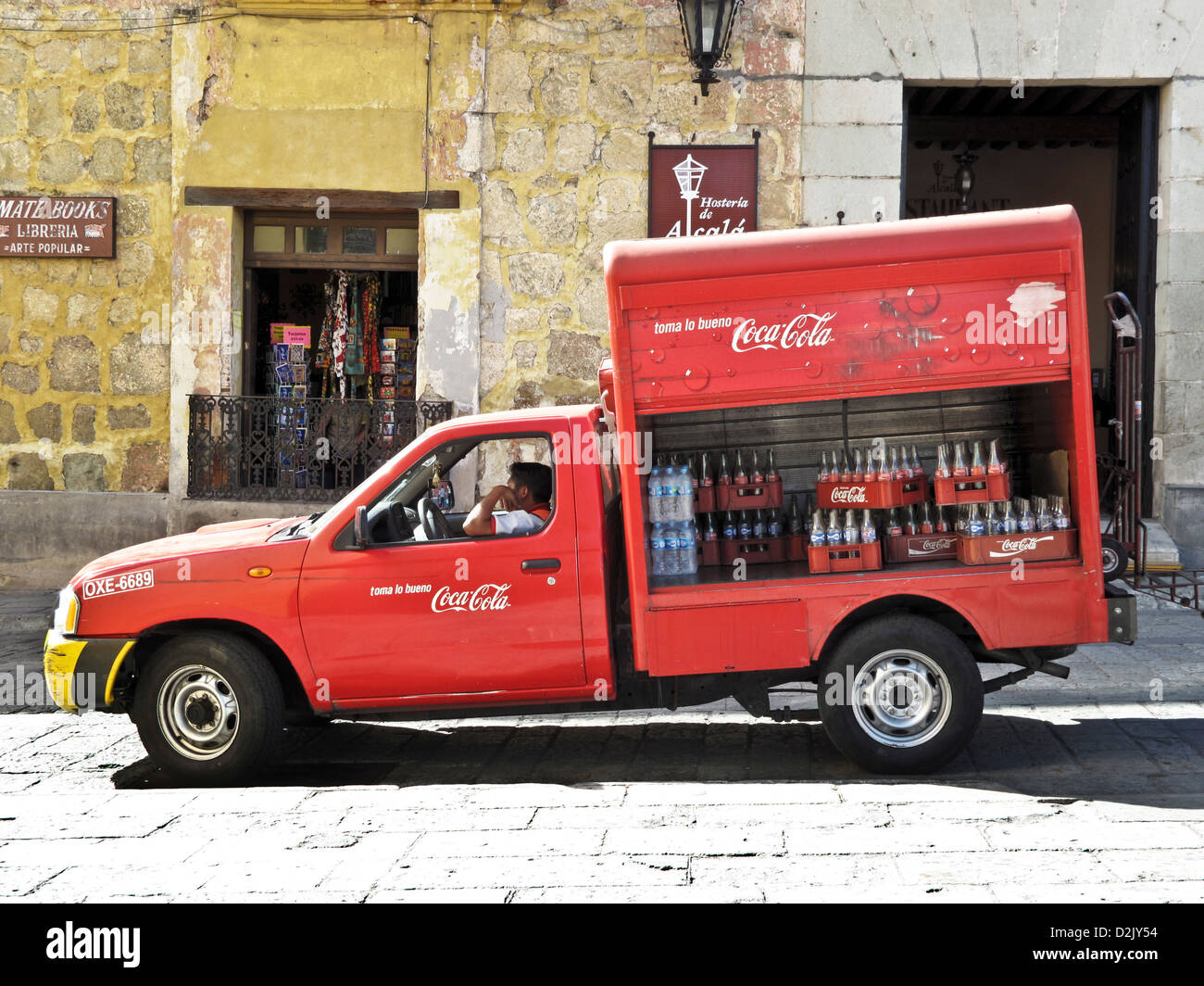 red Coca Cola truck with open side panels revealing crates of empty bottles making a delivery in Oaxaca de Juarez Stock Photo