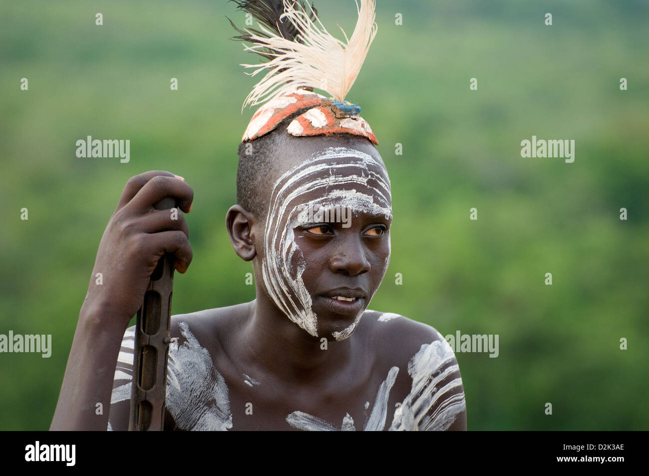 Portrait of Kara man with body painting and headdress-holding rifle - Stock Image