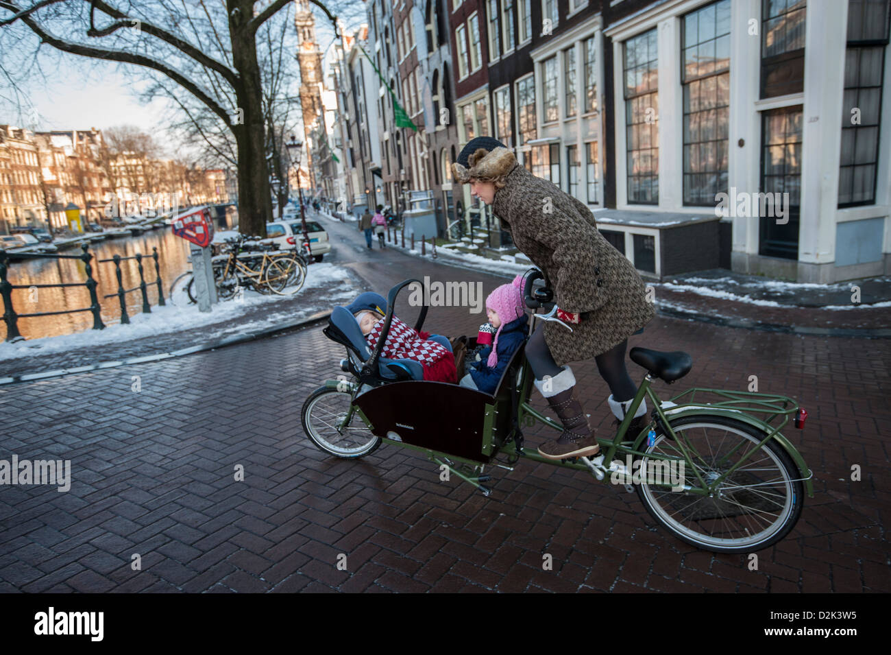 Mother with two kids in bicycle front navigating a slippery winter road along the canal - Stock Image