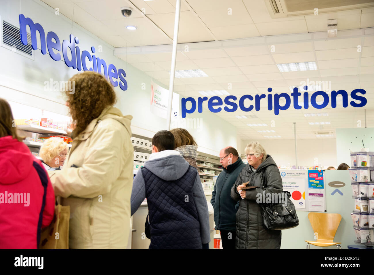 Prescriptions counter inside a Boots shop in Cwmbran, South Wales, UK. People queuing for over the counter medicines. - Stock Image