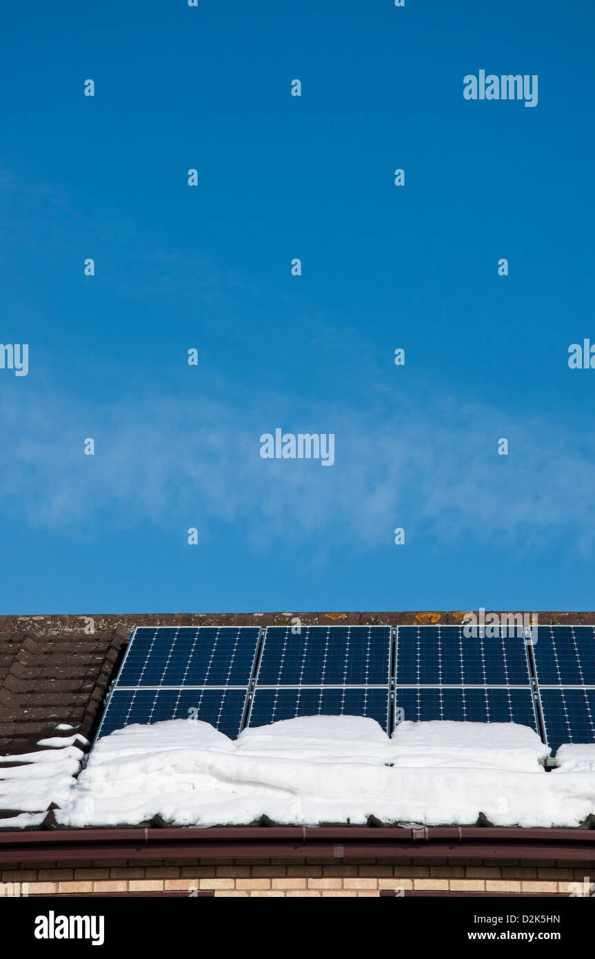 Domestic solar photovoltaic panels on roof of house with snow - Stock Image