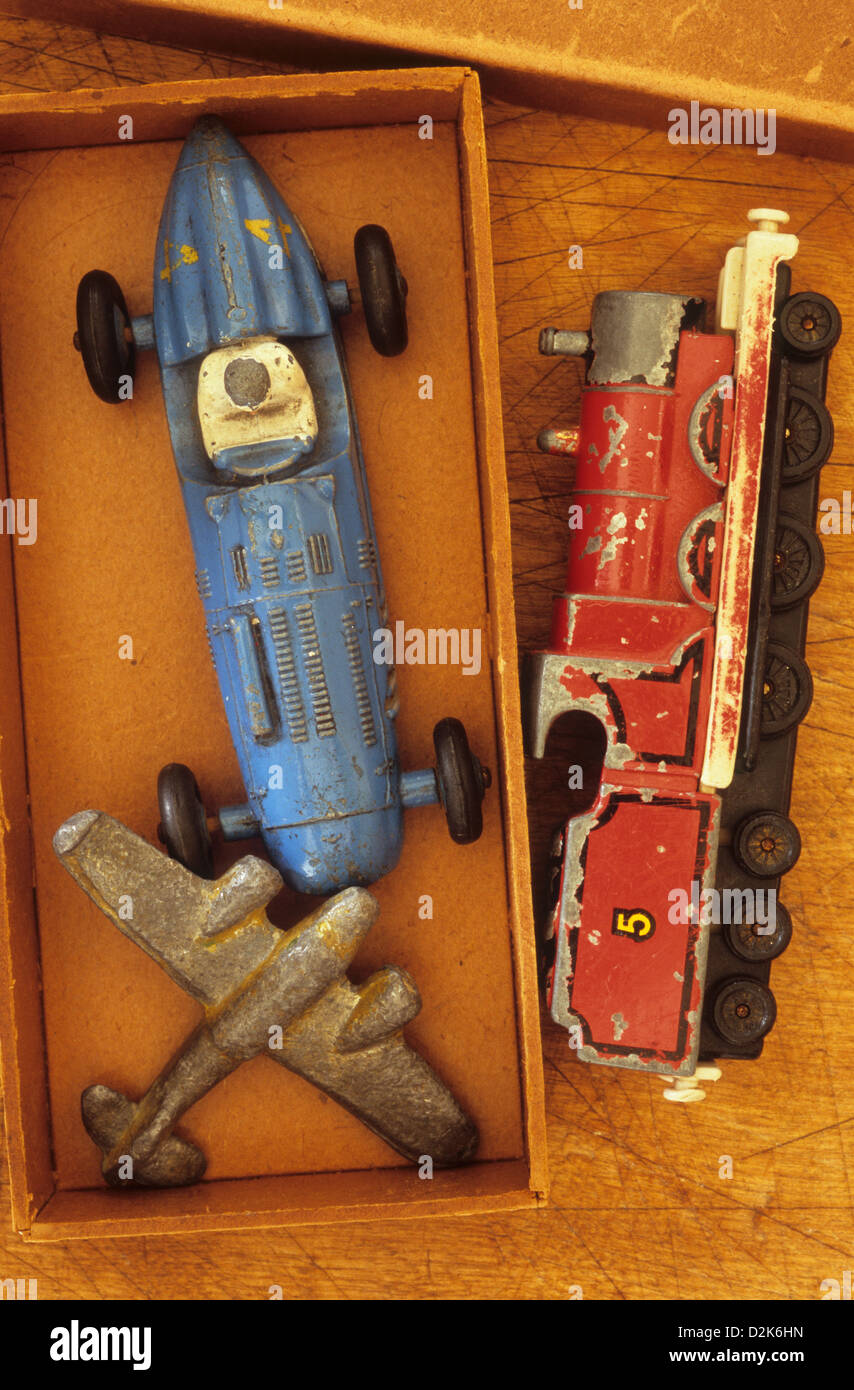 Small cardboard box with battered lead or diecast metal models of aeroplane racing car and steam locomotive Stock Photo