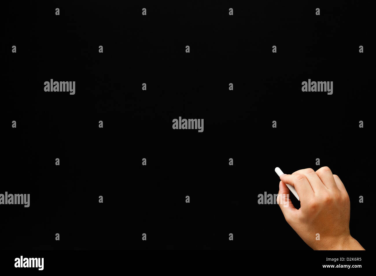 Hand writing something with white chalk on a blank blackboard. - Stock Image